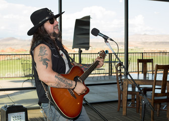 Musician playing guitar and singing at a local club with Sand Hollow Golf Course in the background