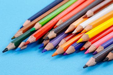 Color pencils on white background. Tools for drawing, education, school, creativity. Set of colored pencils on a blue background.