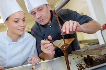 happy male chef and female cook preparing dessert