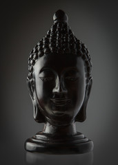 Statue of Buddha head black. isolated dark background.
