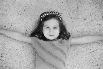 Black and white portrait of a young girl laying on concrete