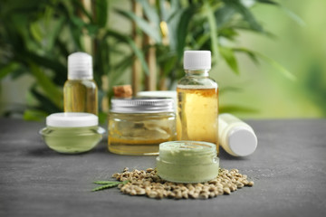 Hemp cosmetic products and seeds on grey background