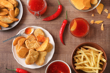 Fast food snacks with chili sauce on wooden background