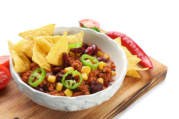 Chili con carne in bowl with chips and vegetables, isolated on white