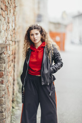 Woman wearing large hip hop trousers and leathr jacket looks at the camera while standing in old village street