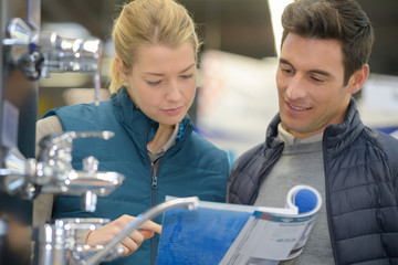 couple looking in catalogue for faucets