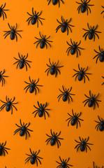 Small black spiders on orange background/miniature.