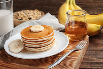 Plate with yummy banana pancakes on wooden table