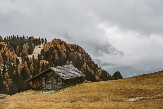 wooden mountain hut in foggy autumnal mountain landscape
