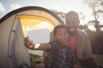 Father and son taking selfie with mobile phone in park