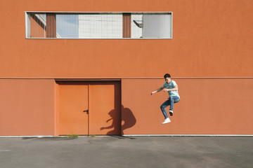 Asian man jumping in urban area