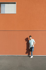 Cool asian man portrait against big orange wall