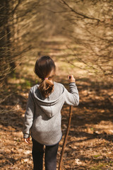 A young girl hiking in the woods with a walking stick