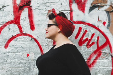Stylish woman in red scarf standing against graffiti wall
