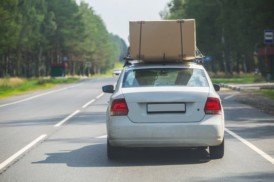 car with cardboard box on the upper trunk is moving along the highway