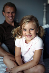Daughter WIth Ponytails Smiling With Dad in Background