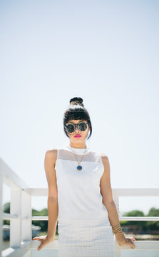 Stylish Asian young woman in white clothes and round sunglasses