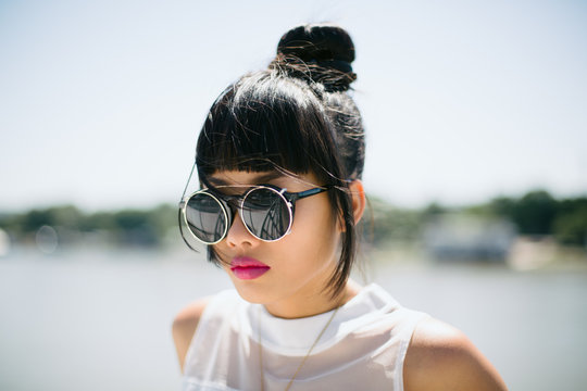 Stylish Asian young woman with round sunglasses and fuchsia pink lipstick