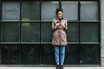 Fashionable woman browsing on her mobile phone