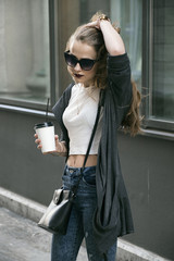 Stylish woman with coffee to go