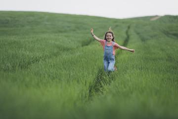 Happy little girl running along green wreath field.