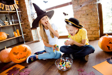 Sweets for us! Treat or trick! Very cheerful excited small kids in carnival head wear, with colorful treats, carved pumpkins, fall leaves, enjoying, sittig on browm wooden floor, casual outfits