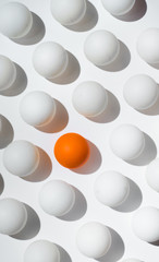 Orange ping pong balls surrounded with white balls one white background .