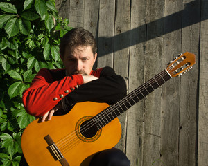 Adult man playing guitar in summer garden