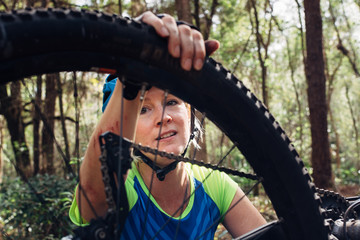 Female mountain biker checking her bycicle tire