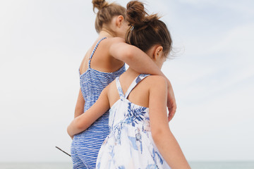 Two girls walking with arms around each other on the beach