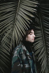 Young woman standing in palm tree leaves at sunset