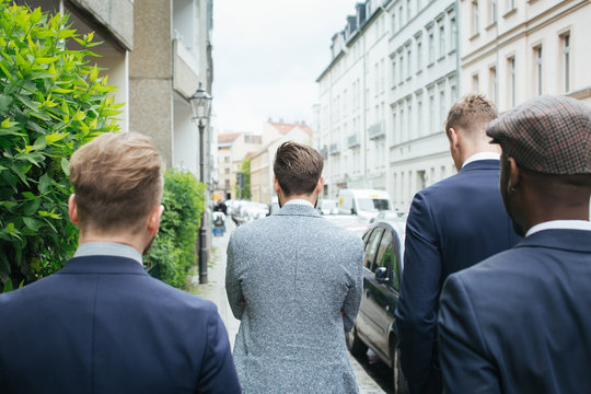 Group of Four Stylish Young Men in Suits Walking Down Street