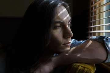Portrait of young middle eastern man looking out window with bands of light on face
