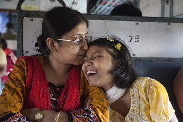 Indian woman kisses her daughter in a local train travel