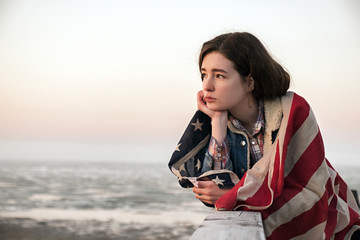 Portrait of sad brunette in Amercian flag watching sunrise