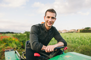 Portrait of a man with tractor in a green field.