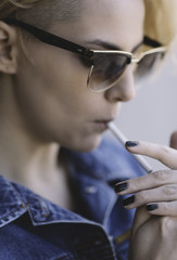 cool young woman lighting cigarette
