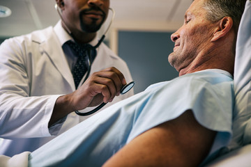 Hospital: Doctor Leans In To Listen To Heart