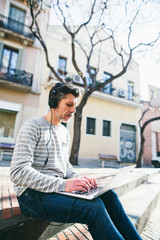 Casual mature man working with his laptop on the street.