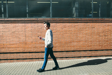 Side view of a mature man holding his phone walking in the city.