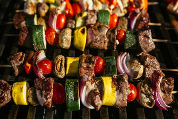 Chicken, steak and vegetable skewers on a grill