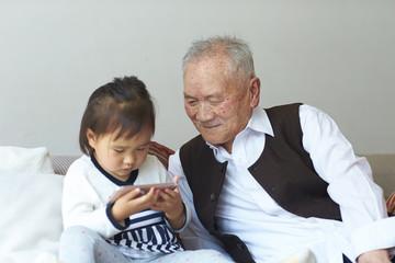 senior asian man watching his great granddaughter using smart phone
