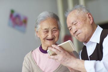 senior asian couple using smart phone indoor