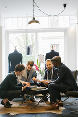 Men's Fashion - Four Stylish Young Men in Suits Looking at Suit Fabrics