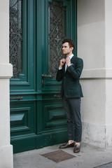 Street Portrait of Fashionable Caucasian Man Adjusting Bow Tie