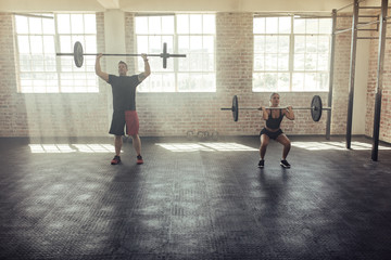 Young people exercising with barbell at gym