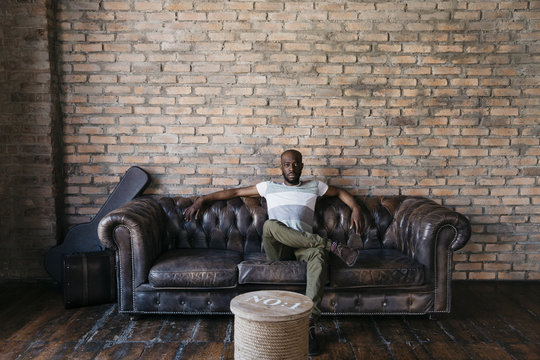 Black man looking at camera from a couch
