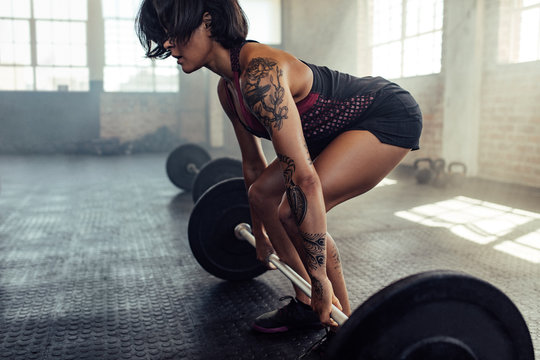 Tattooed woman working out with barbell at gym
