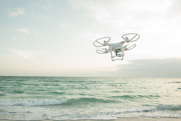 Drone flying over sea against sky