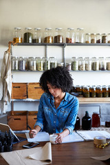 Businesswoman writing on check in her skincare studio